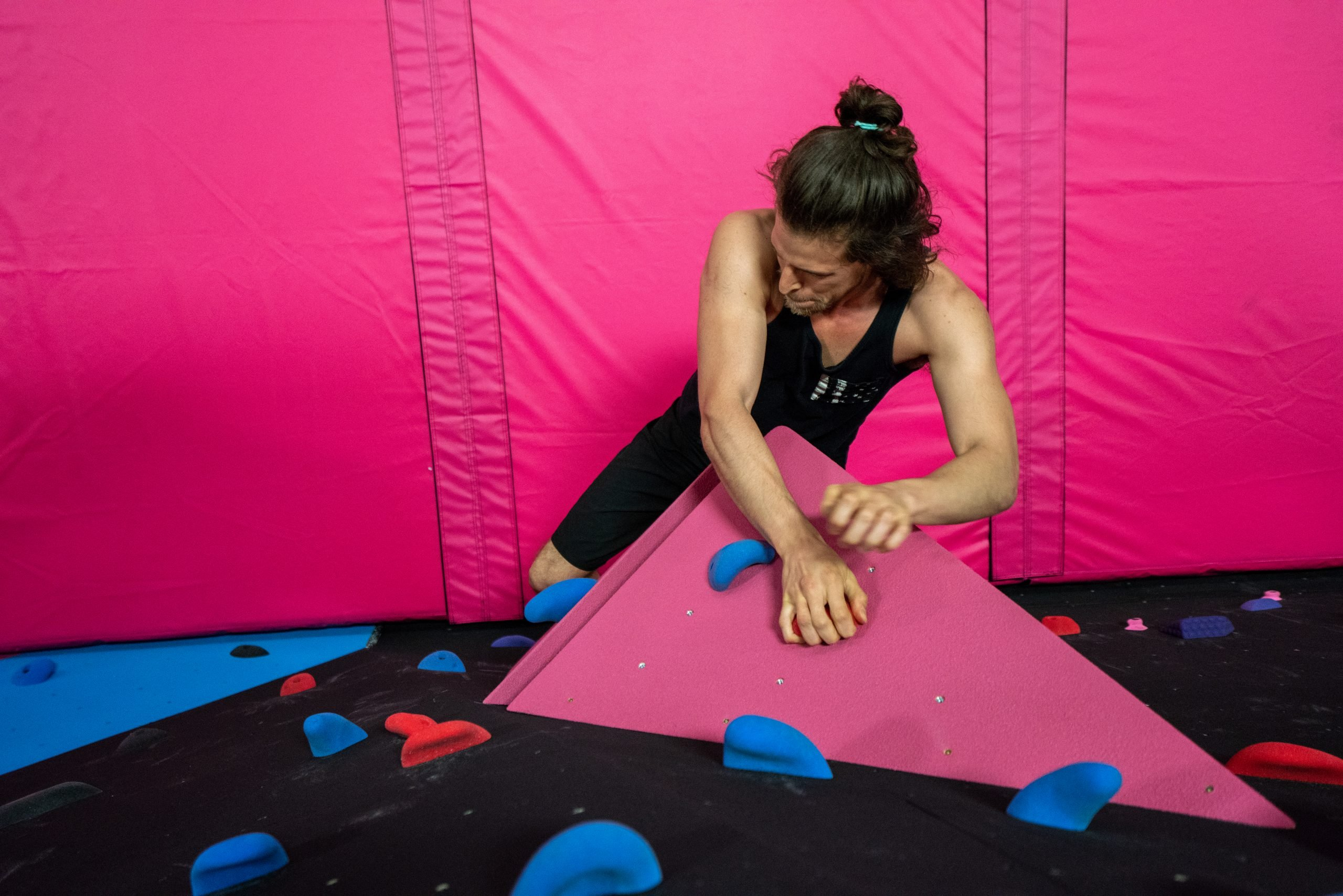 Small bouldering wall, with overhang, volumes and Canada Crash Pads, custom in pink