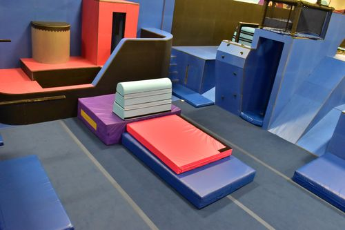 Custom tiered foam shapes with various Canada Crash Pad custom designs, on springboard floor and parkour structures.  Someone's been having some fun here!